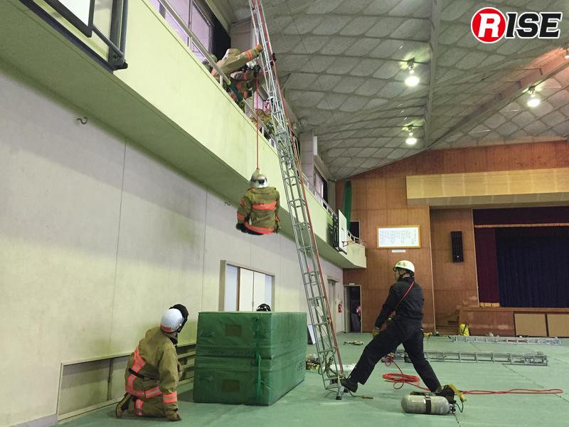 基本形の応急はしご。三つ打ちロープを三連はしごに通し、索端の三重もやいで身体縛着を実施。肩確保で救助ロープを操作する。
