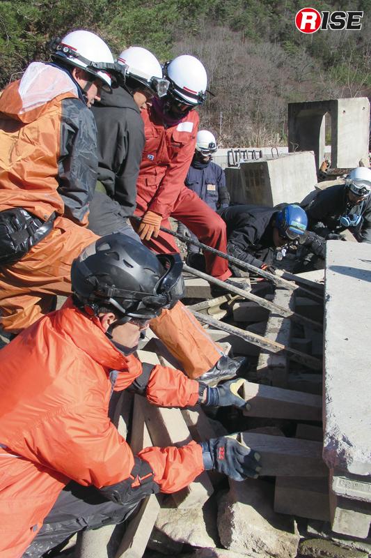 重いコンクリート板をバールで浮かせその下にクリブを挿入する。
