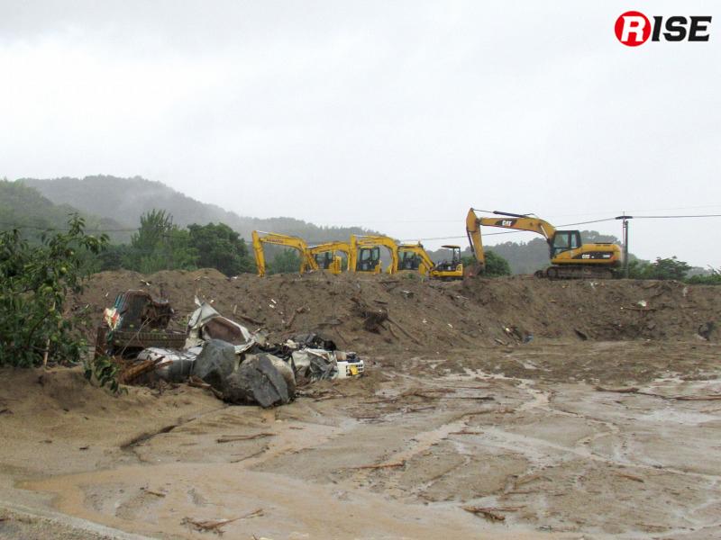 土砂の排除などを行う重機。手前には無残な姿となった自動車が横たわる。