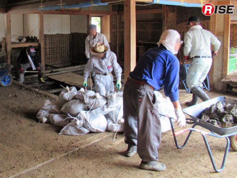 土砂は一輪車や土嚢袋を用いて人力で屋外へ搬出する。