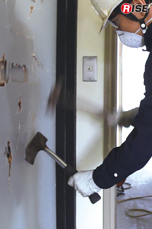 手とハンマーで中空ドアの切開を行う。
