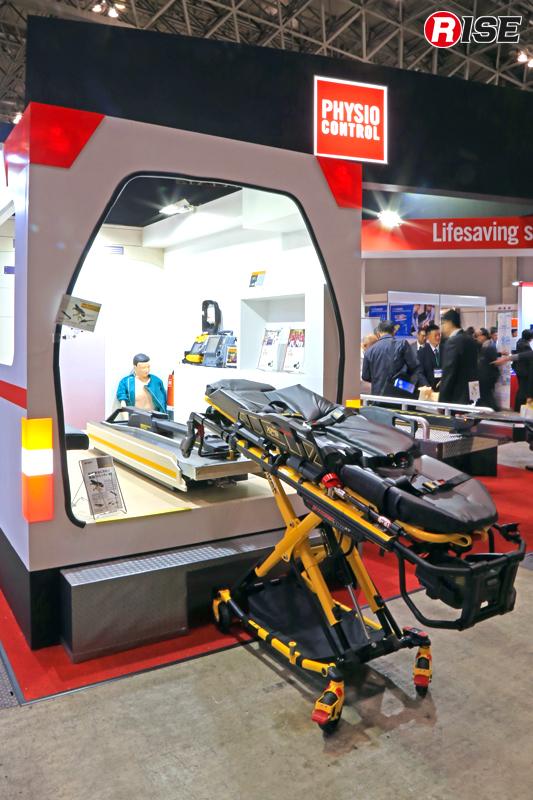 国産救急車を模した展示ブース。日本ストライカー株式会社の電動ストレッチャー「Power Pro XT 6506」と専用手動ファスナー、株式会社赤尾の「VCS-02防振架台」の車載イメージが確認できる。