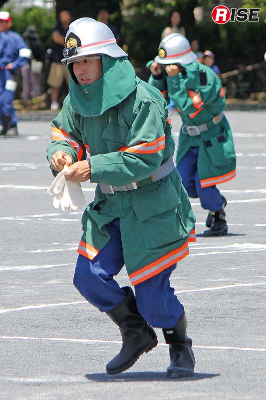 防火衣着装訓練は障害物競走のように防火衣・防火帽・手袋・鳶口の流れで順次装備をつけていく。
