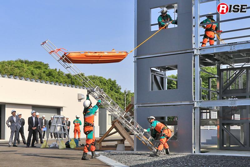 三連はしごを倒し込み、はしご水平救助第一法の要領で救出する。