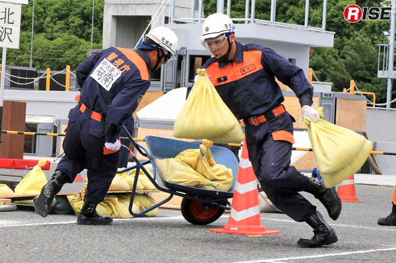 徒手及び一輪車を用いて土嚢を搬送する。