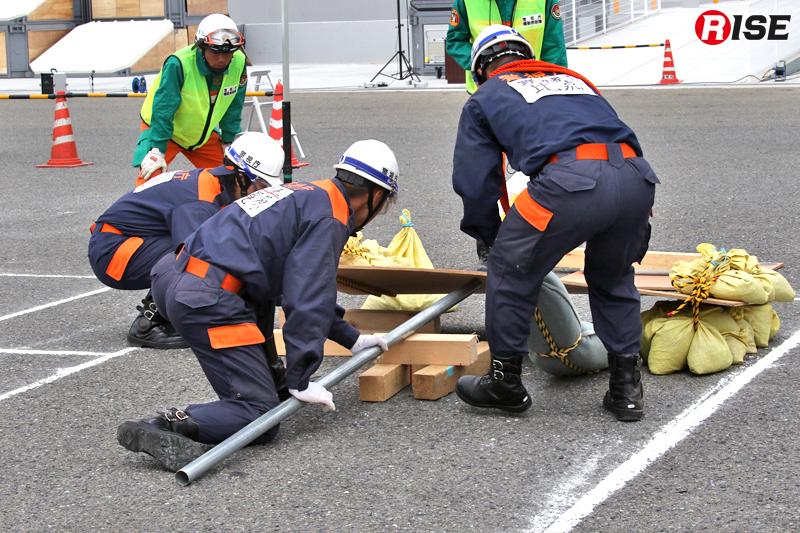 重量物の下敷きとなった要救助者(ダミー)を単管パイプなどを活用し、てこの原理で救出する。