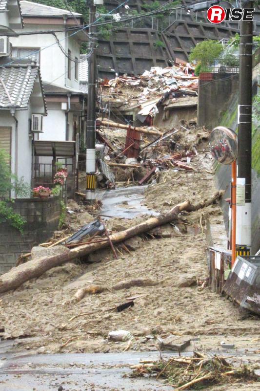 梅河団地の状況。治山ダムを突破した土石流が道路を駆け抜けた。