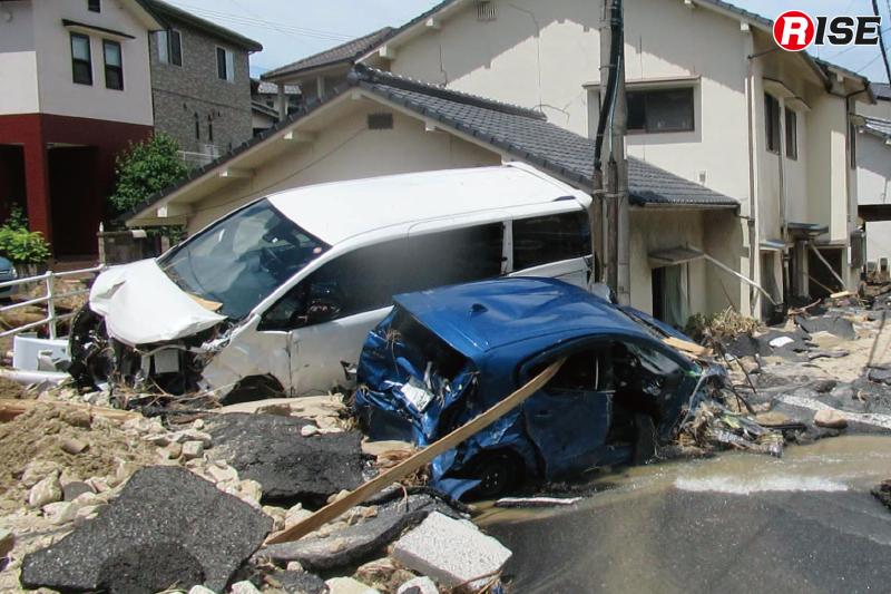 流された車両が住宅に衝突し折り重なるように留まっている。