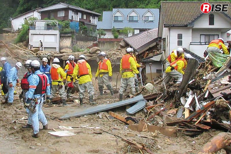 倒壊した住宅の内部検索を図るべく瓦礫などを丁寧に取り除き、一列に並びリレー方式で搬出する隊員ら。