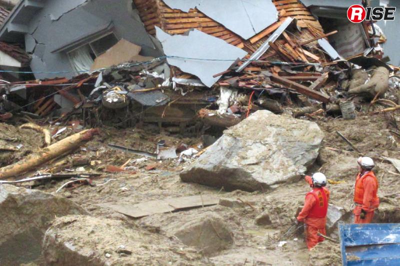 景色が一変した住宅街にて破壊された家屋の状況を確認しながら捜索活動を実施する広島市消防局の救助隊員。