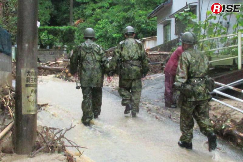 捜索活動のため川のように雨水が流れる道路を進む自衛隊員。