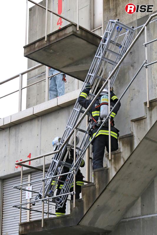 屋外階段により三連はしごを徒手搬送している例。