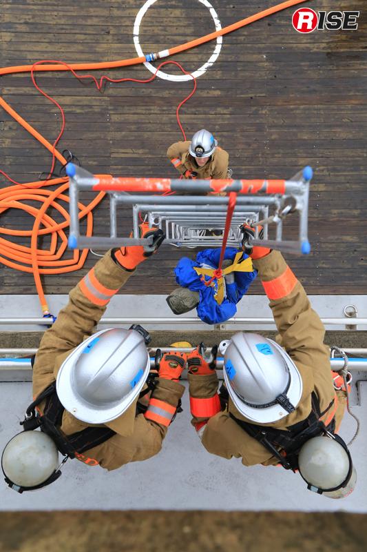 上階の要救助者を応急はしごの要領で救出する。