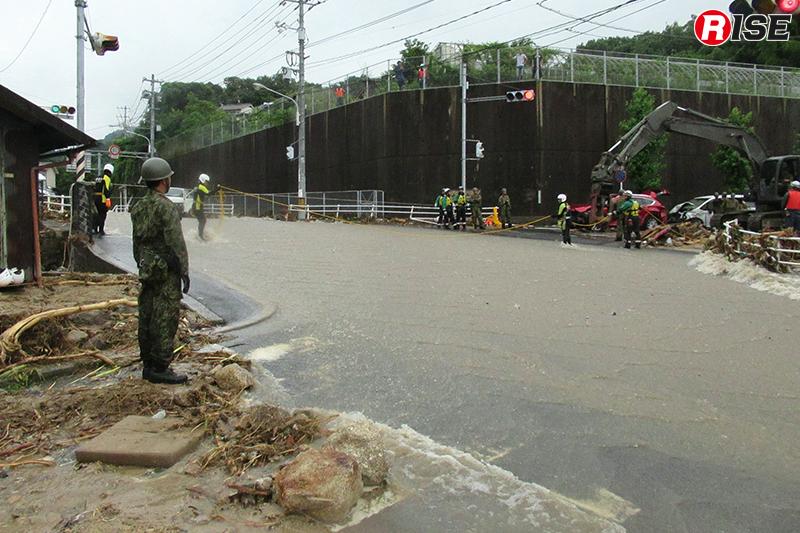 濁流が流れる県道34号線の天神交差点。水難装備を着装した警視庁の救助隊員が親綱を設定し往来の補助を行っていた。