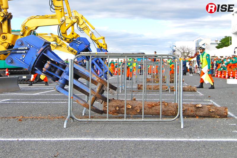 鉄柵に重機のつかみ機が触れぬように慎重に操作を行う。