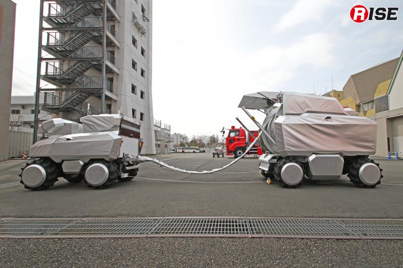 あらかじめ放水砲ロボットにホース延長ロボットのホースを結合した状態で部署位置まで移動する。