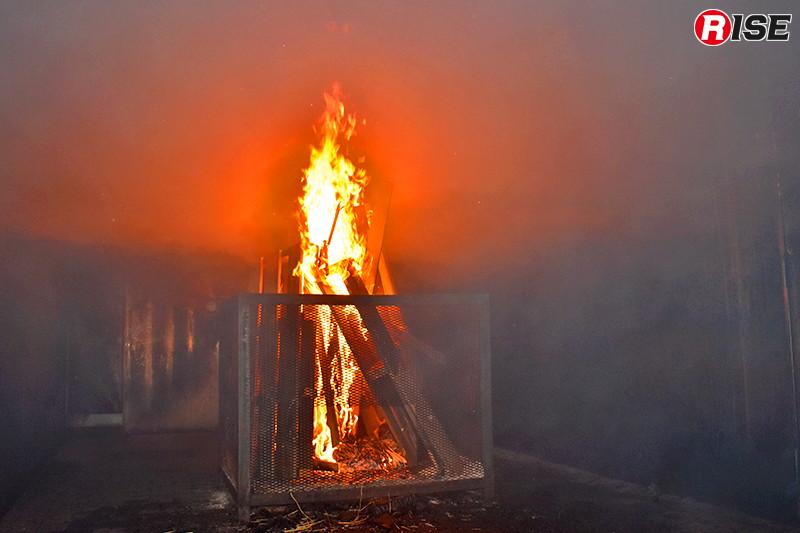室内を濃煙熱気が満たしたところで、外部から環境改善のための放水を実施。