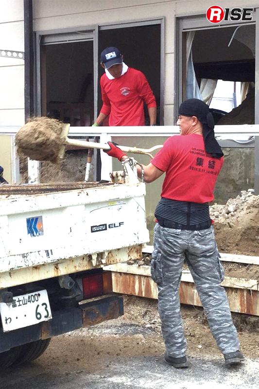 アパートの室内に堆積した土砂を除去しダンプへと積み込む。