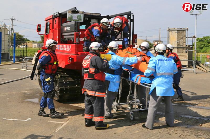 待機する救急隊に要救助者が引き継がれる。