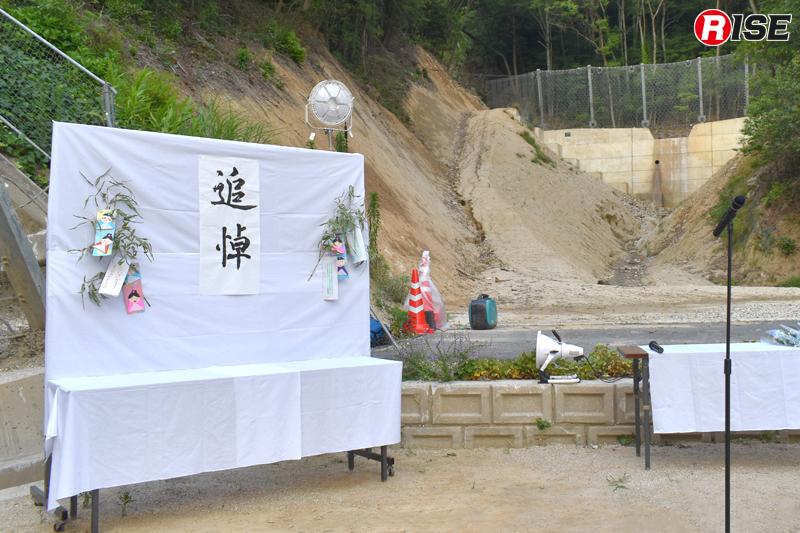 献花台の奥に見えるのが治山ダム。不安定になった土砂やコアストーンが流れ出した際に受け止める防護柵が新たに設置されている。