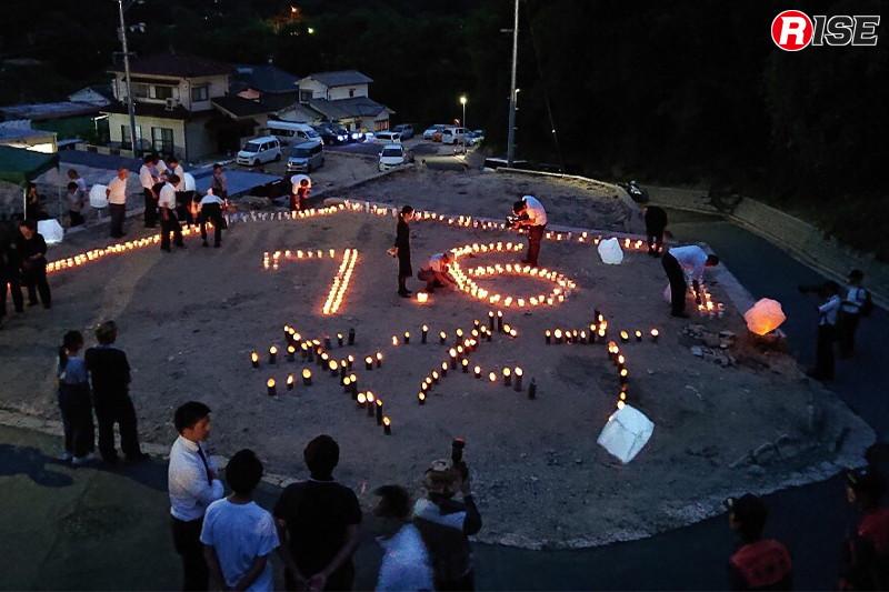 約300個のろうそくにより「7.6キズナ」の文字を浮かび上がらせ、冥福を祈った。