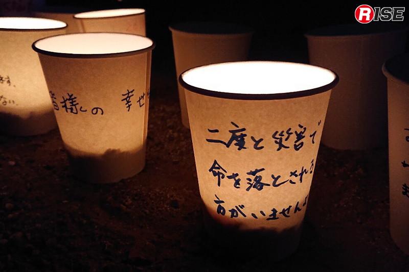 遺族や被災した人々が紙コップにメッセージを書き、中にろうそくを入れて並べた。