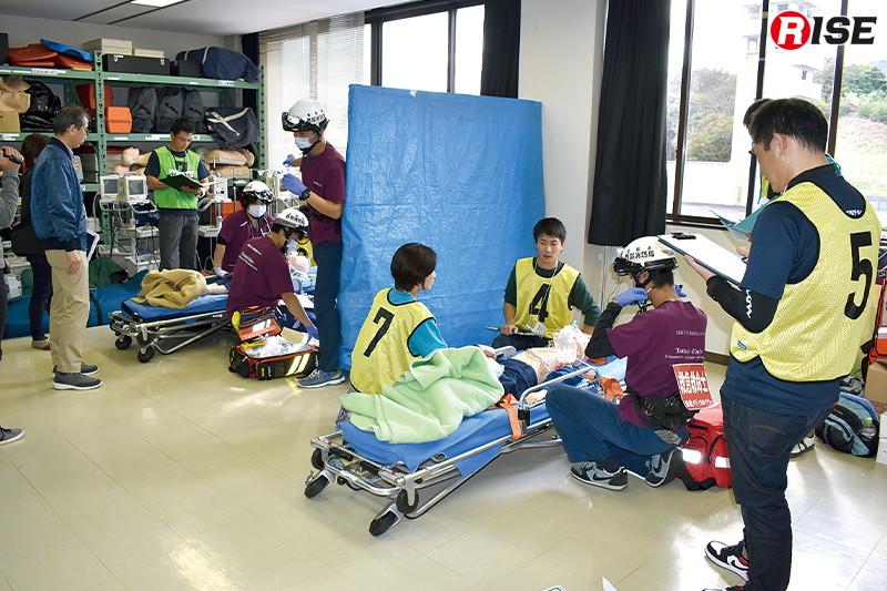 【小児救急ブース】運動会で児童が突然呼吸困難を起こしたとの想定。その横では15歳の中学生が脱水によりショック状態に陥っている。救命士による静脈路確保が可能な年齢、ルート確保の選定がポイント。