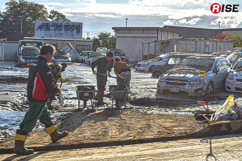 中古車販売店で堆積した土砂を除去する関係者。