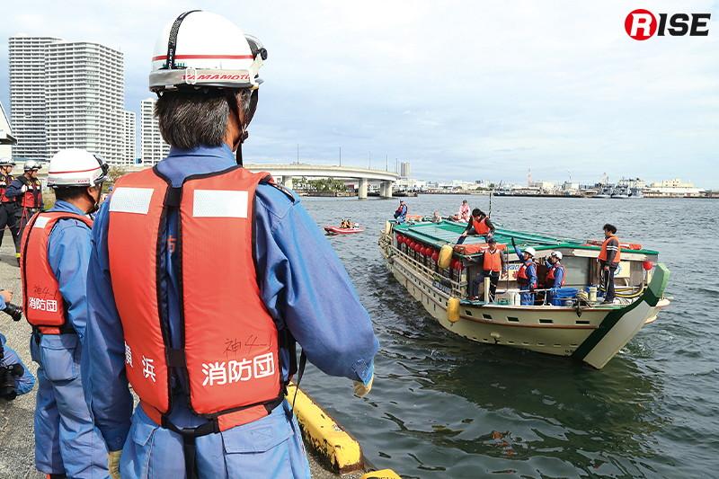 移送されてくる旅客船乗客を待つ消防団員。