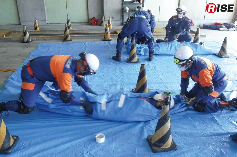 【長久手市/瓦礫救助想定】要救助者の保護と保温を目的に行うシートパッキング。三角コーンの間を活動可能範囲として訓練を行う。