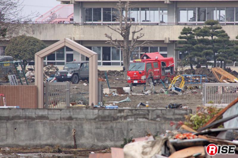震災当時の閖上小学校。水が引き、瓦礫が除去され、津波被害にあった閖上分団第9部の消防団救助資機材搭載型車両が見える。