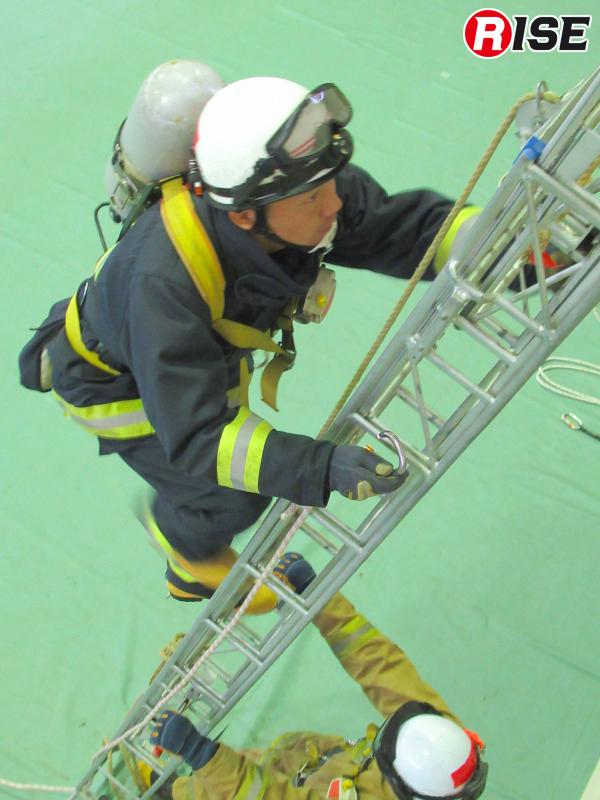 つるべを設定する際は、横桟にかけるオートロック式カラビナをゲートオープンの状態で保持したまま登梯。これも時短テクのひとつ。