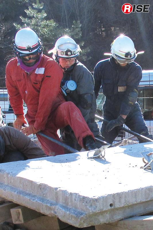 3名が息を合わせバールでコンクリート板を浮かせる。