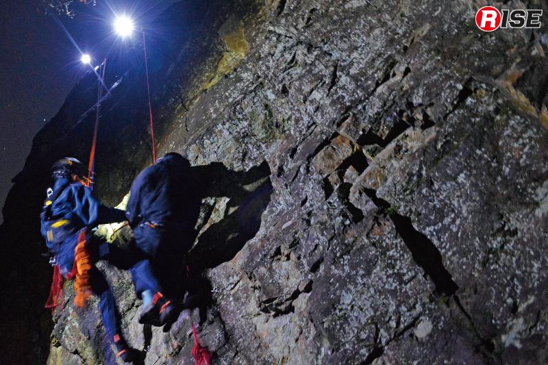暗闇に支配された岩場にて、ヘッドライトの明かりを頼りに救出活動を行う。