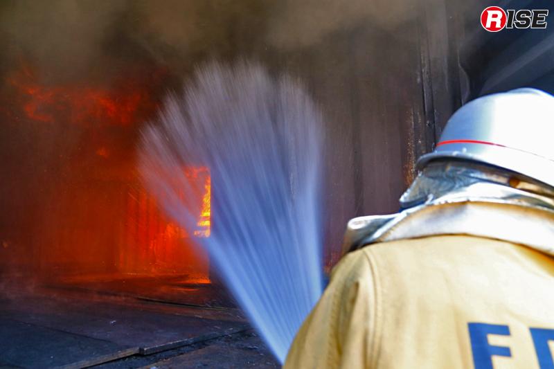 フラッシュオーバーの兆候を確認した場合に実施する「攻撃的冷却注水(アグレッシブクーリング)」。写真はノズル角60度の噴霧を上方に向ける「スポット注水」と呼ばれるもの。熱成層を崩さないよう出来るだけ短時間の注水を数回行い、熱を吸収させガス冷却を実施する。