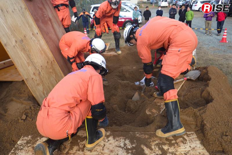 活動隊員の足元にはグランドパッドを敷き、山側からの土砂流入をコンパネにより止める。