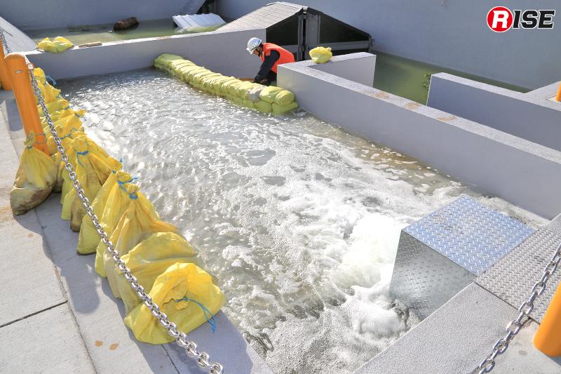 きちんと積み上げた土嚢が水圧に負けることなく水の流出を防いでいる。