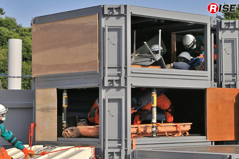 要救助者をバックボードに縛着し、1段下に準備したバスケット担架へ収容する。