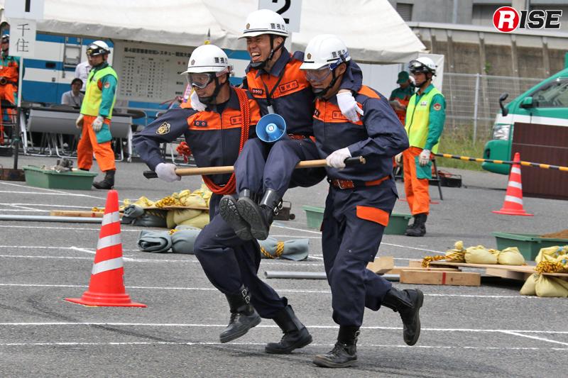 警杖2本を活用し、要救助者(生体)役の指揮者を搬送する。