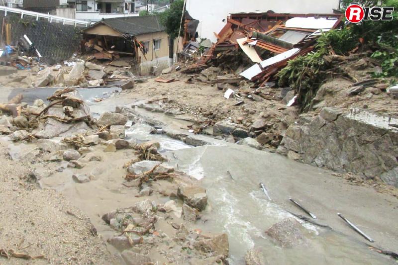 上流では山からの水が道路を流れ続けている。