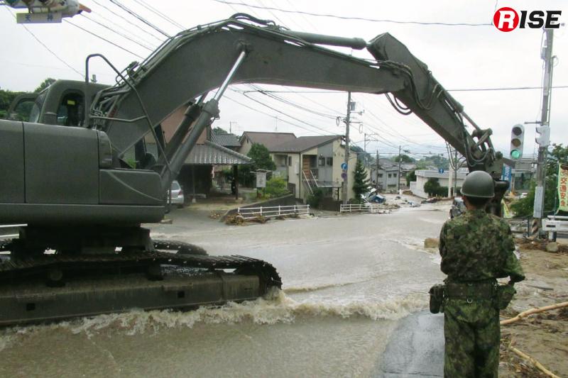 自衛隊が重機により道路啓開を行う。