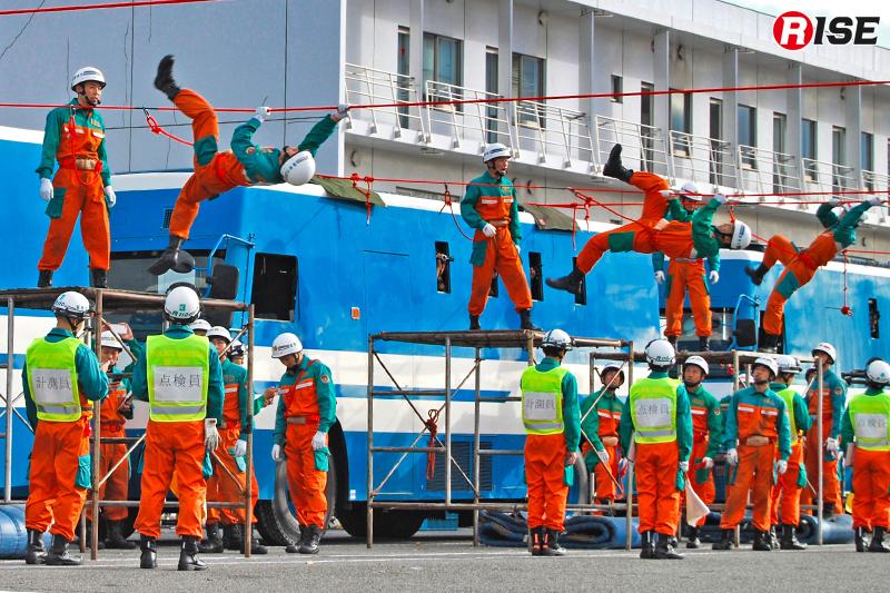 警備車両の車上に展張した20mのロープを舞台に実施される渡橋競技。