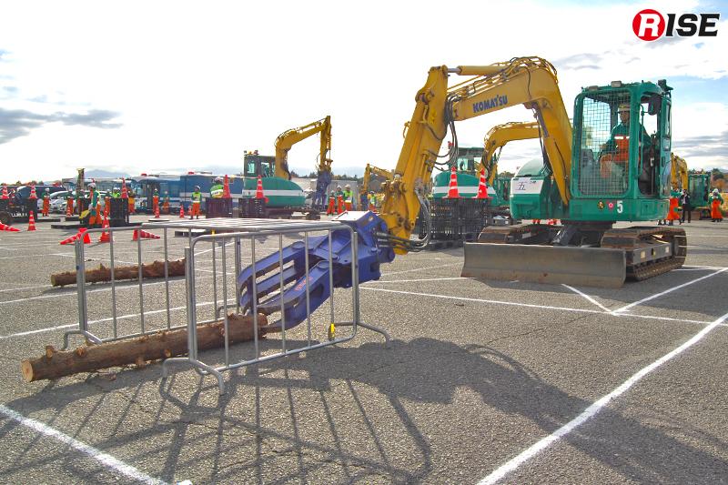 鉄柵で作られた空間内にある丸太を重機により除去する。
