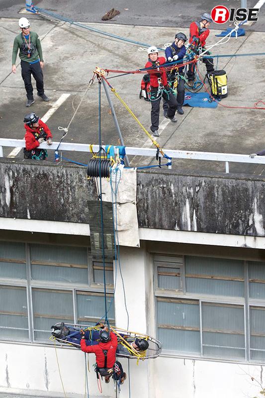 ハングのある場所において宙吊りの要救助者を担架でスクープして上げる想定。