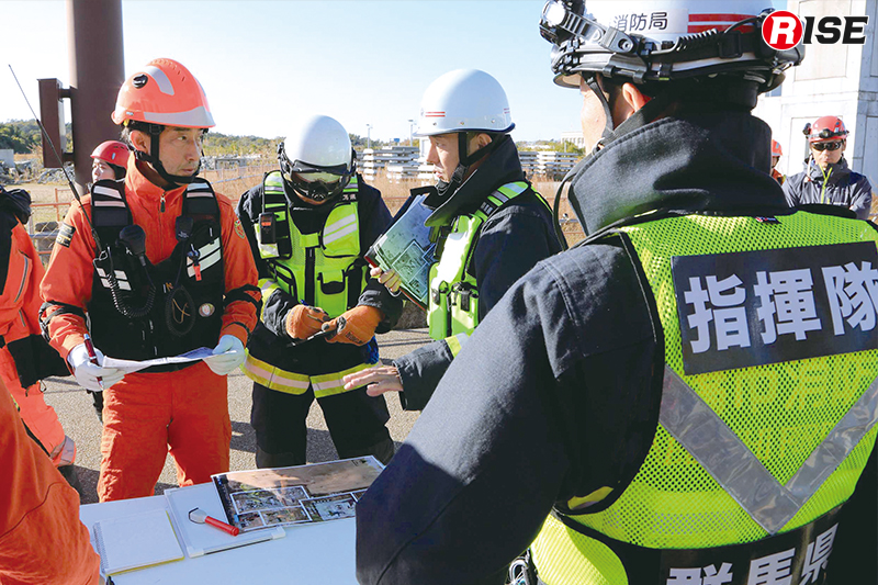 現場指揮本部にて消防指揮隊の下命を受ける救助犬チーム。