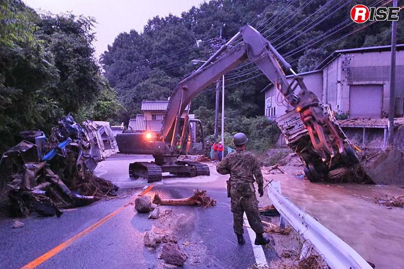1年前:河川に落ちたトラックが氾濫を招き、道路に流れ出した水が捜索活動を阻んでいた。