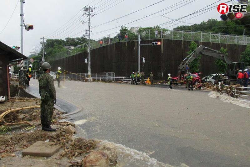 1年前:濁流が流れる県道34号線の天神交差点。水難装備を着装した警視庁の救助隊員が親綱を設定し往来の補助を行っていた。