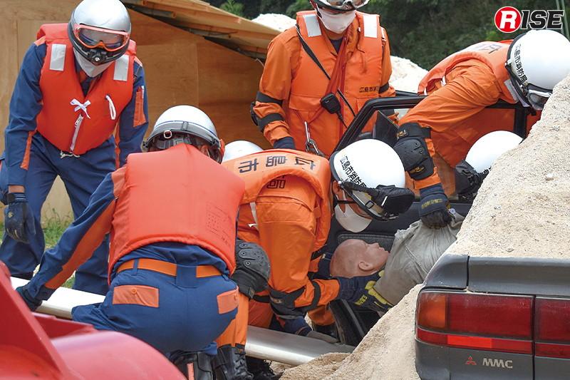 埋没車両内で要救助者を発見。署団が連携し救出にあたる。
