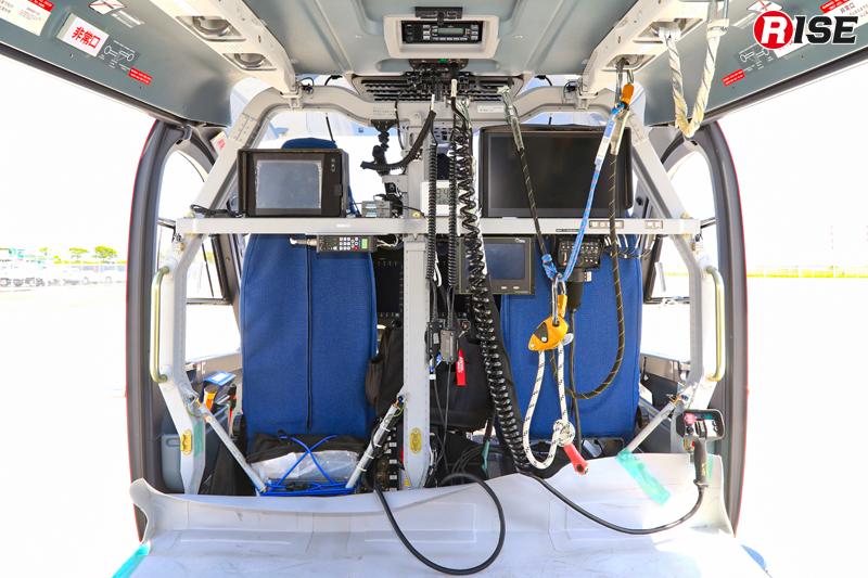 操縦席背面には無線機や各種モニターが並ぶ。写真右側のモニターがヘリコプターテレビ伝送装置用で、機外のカメラで撮影した映像を県庁や市町、各消防本部へ伝送できる。写真左側のモニターが総務省消防庁が無償使用制度により配備を行っているヘリコプター動態管理システムの機体端末。