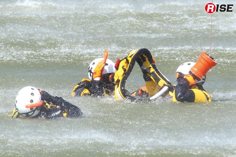 要救助者役の隊員に接触。ヘリを直上におくことでダウンウォッシュの影響を低減させ、迅速に縛着する。